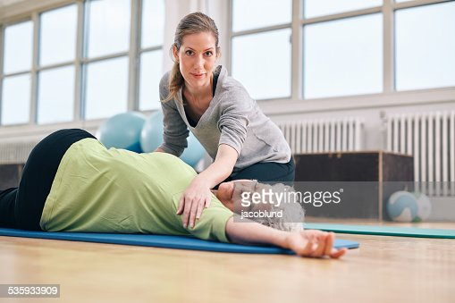 Trainer helping senior woman in her stretching workout : Stock Photo