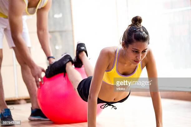 Trainer helping young woman exercising in gym
