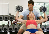 Trainer helping young woman weight train in gym