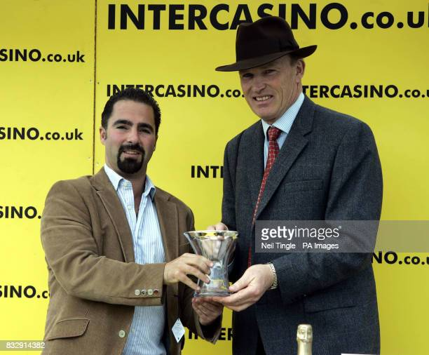 Trainer John Gosden receives the trophy after victory with Imperial Star in the Intercasinocouk Magnolia stakes at Kempton Racecourse