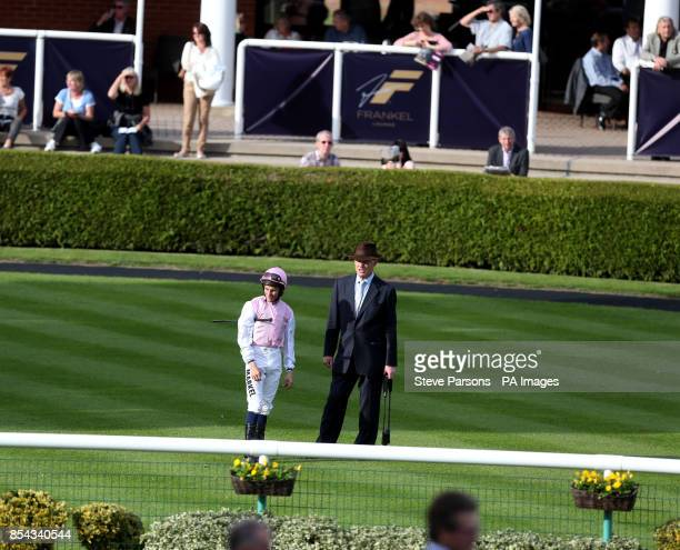 Trainer John Gosden stands in the parade ring with Jockey William Buick before the Jockey Club Rose Bowl race during day one of the 2013...