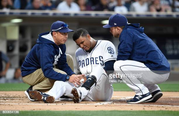 A trainer left and manager Andy Green right look at Allen Cordoba of the San Diego Padres after he was hit with a pitch during the third inning of a...