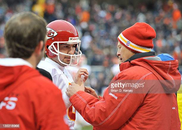 A trainer looks at the hand of quarterback Kyle Orton of the Kansas City Chiefs on the sideline against the Chicago Bears at Soldier Field on...