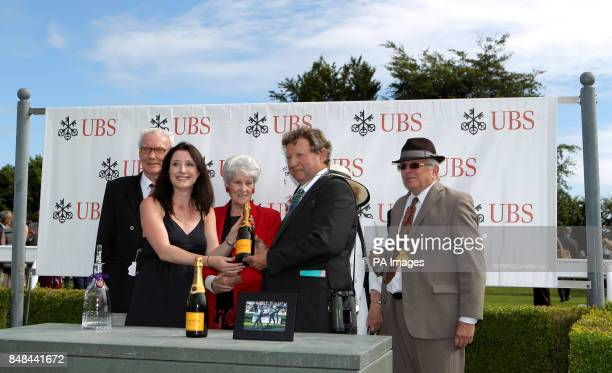 Trainer Mark Johnston is presented with an award after Sir Graham Wade won the UBS Handicap