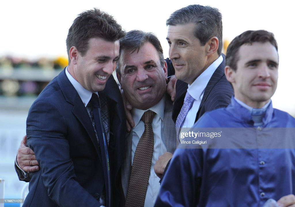 Trainer Mark Kavanagh is hugged by his son Levi Kavanagh and part owner Laurie Macri (r) after the win of Atlantic Jewel in the New Zealand Bloodstock Memsie Stakes during Melbourne racing at Caulfield Racecourse on August 31, 2013 in Melbourne, Australia.
