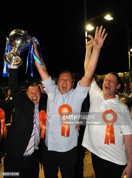 Trainer Mark Wallis assistant trainer Patrick Jamssens and Gary Budger celebrate as Kinda Ready wins the Greyhound Derby Final at Wimbledon dog track...