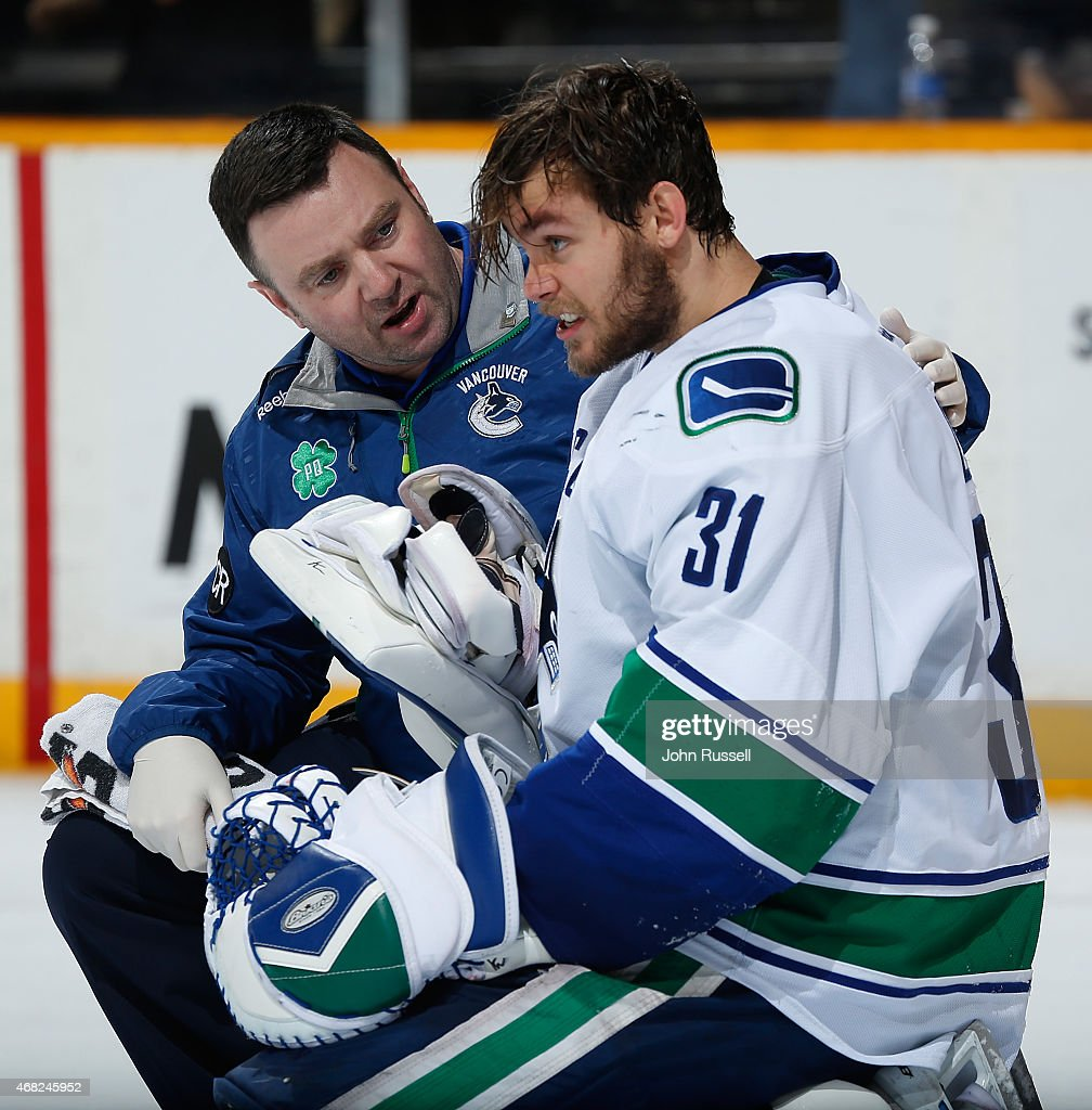 Trainer Mike Burnstein checks on Eddie Lack #31 of the Vancouver Canucks after a hit to the head against the Nashville Predators during an NHL game at Bridgestone Arena on March 31, 2015 in Nashville, Tennessee.