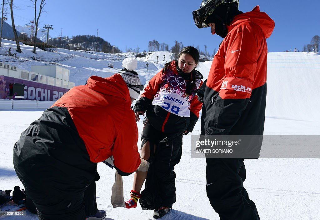 A trainer of Paraguay's slopestyle skier Julia Marino (C) wraps a bandage around with her leg during a training session at the Rosa Khutor Extreme Park on February 5, 2014 ahead of the 2014 Sochi Winter Olympics.