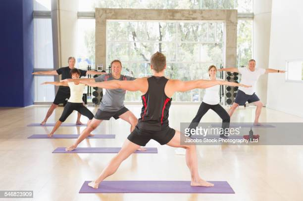 Trainer practicing yoga with class in gym