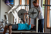 Trainer provides assistance to man lifting weights