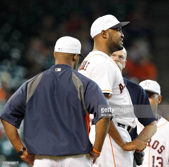 Trainer Rex Jones and manager Bo Porter check on Jose Veras of the Houston Astros who had a ball hit off his hand during action against the Tampa Bay...