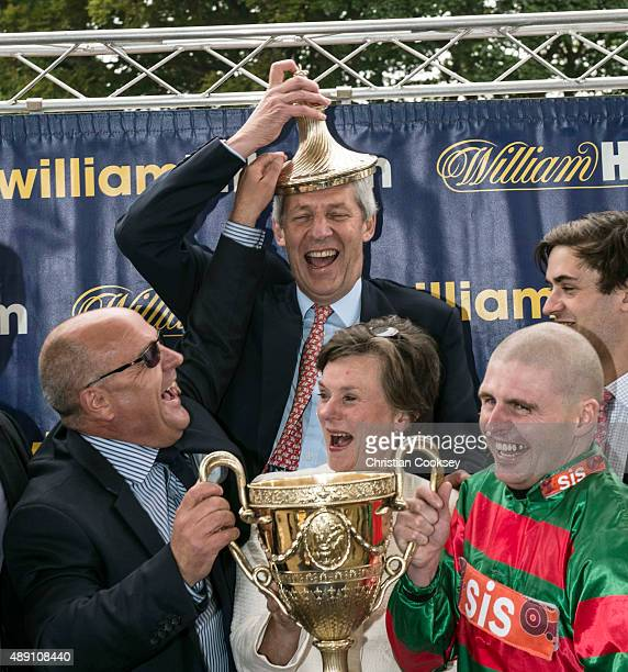 Trainer Richard Fahey puts the lid of the Ayr Gold Cup on the head of joint owner Nicholas Wrigley after jockey Tony Hamilton rode the winner Don't...