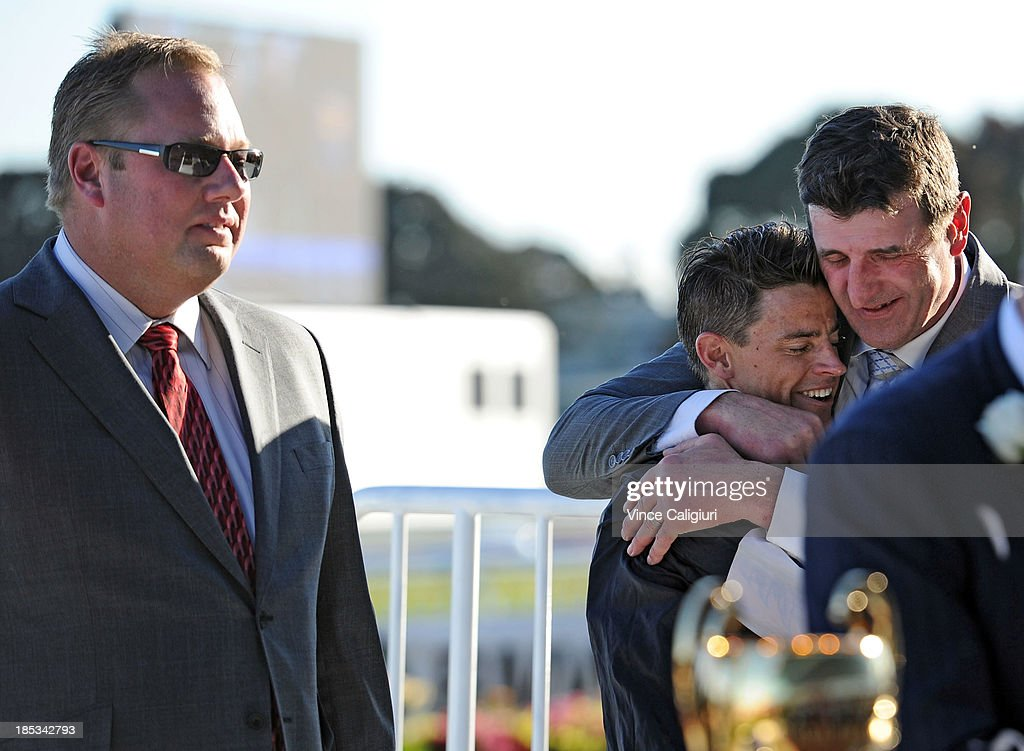 Trainer Robert Hickmott hugs Nicholas Hall after riding Fawkner for owner Nick Williams (L) to win the BMW Caulfield Cup during Caulfield Cup day at Caulfield Racecourse on October 19, 2013 in Melbourne, Australia.
