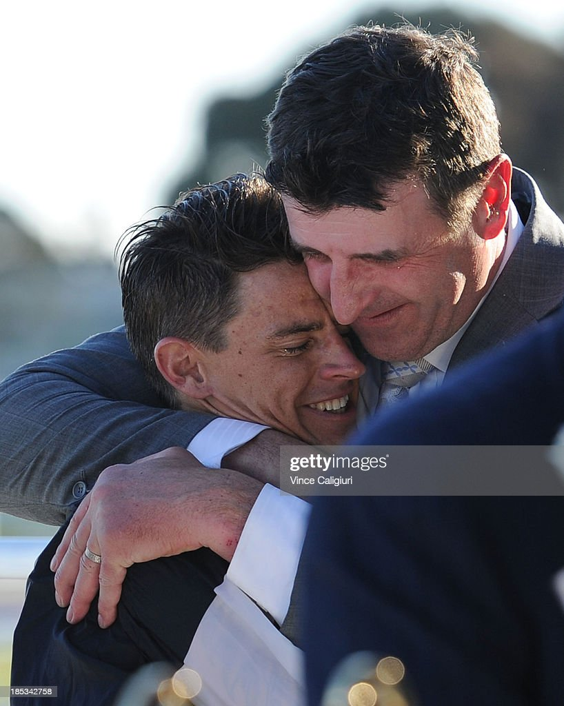 Trainer Robert Hickmott hugs Nicholas Hall after riding Fawkner to win the BMW Caulfield Cup during Caulfield Cup day at Caulfield Racecourse on October 19, 2013 in Melbourne, Australia.