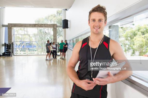 Trainer smiling with clipboard in gym