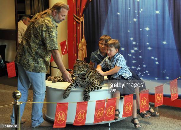 A trainer soothes a leopard during a photo session with children during a show intermission in Moscow circus on Tsvetnoy Boulevard late on July 24...