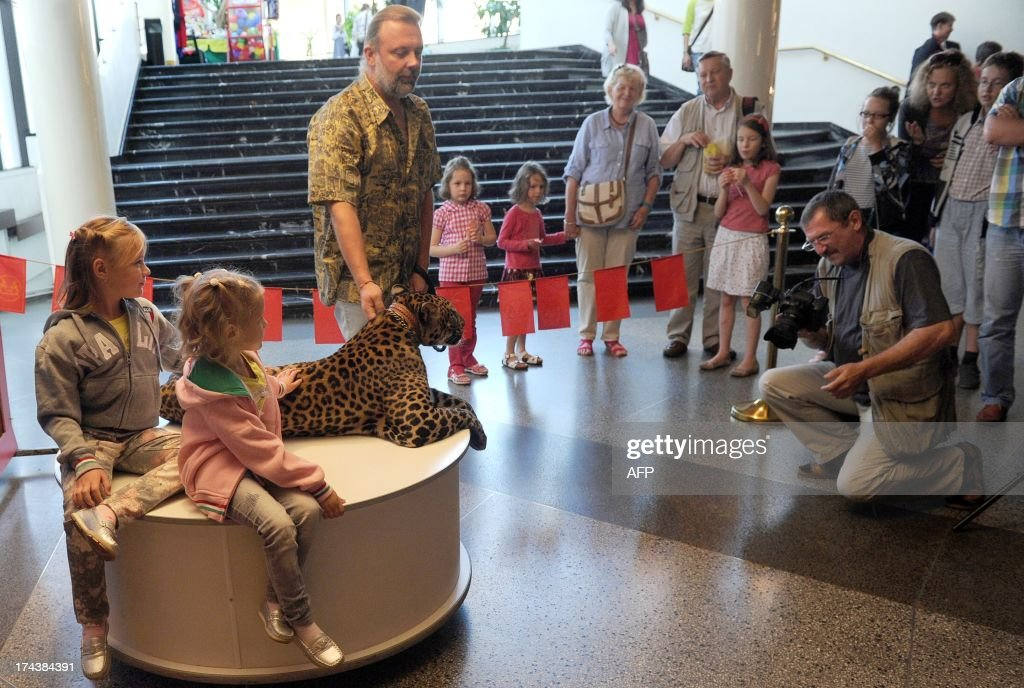 A trainer soothes a leopard during a photo session with children during a show intermission in Moscow circus on Tsvetnoy Boulevard late on July 24, 2013 .