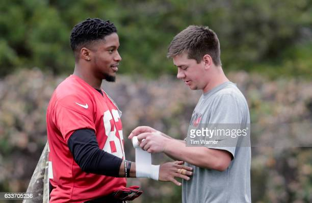 A trainer tapes the wrist of Josh Perkins of the Atlanta Falcons during the Super Bowl LI practice on February 3 2017 in Houston Texas