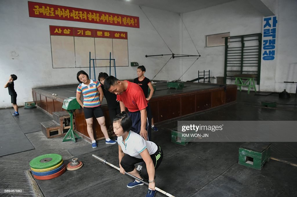 A trainer teaches a young trainee how to lift at the Kigwancha Sports Team gym the home facility where North Korean weightlifter Rim JongSim who won...