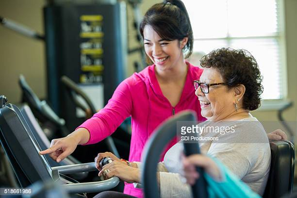 Trainer teaches senior client how to use machine at gym