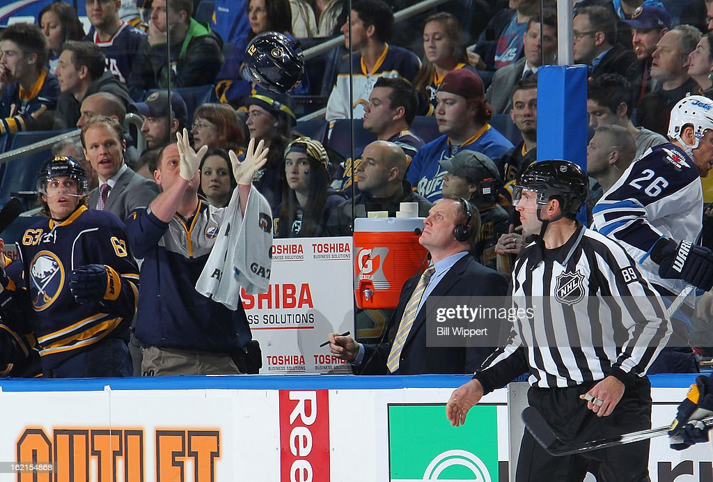 Trainer Tim Macre of the Buffalo Sabres reaches to catch a helmet tossed to him by linesman Steve Miller #89 as broadcaster <a gi-track='captionPersonalityLinkClicked' href=/galleries/search?phrase=Rob+Ray+-+Hockey+Player&family=editorial&specificpeople=228534 ng-click='$event.stopPropagation()'>Rob Ray</a> looks on during a game against the Winnipeg Jets on February 19, 2013 at the First Niagara Center in Buffalo, New York. Winnipeg defeated Buffalo, 2-1.