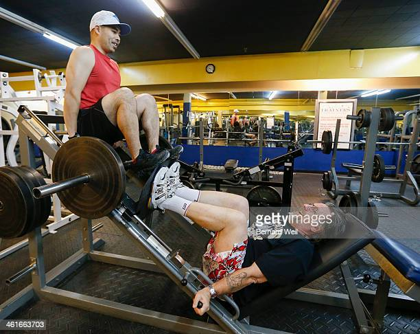 TORONTO ON JANUARY 9 Trainer Tony Tam sits atop a leg press machine while Bill Taylor does his reps January 9 2014