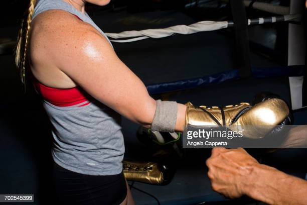Trainer tying boxing glove laces for female boxer in gym