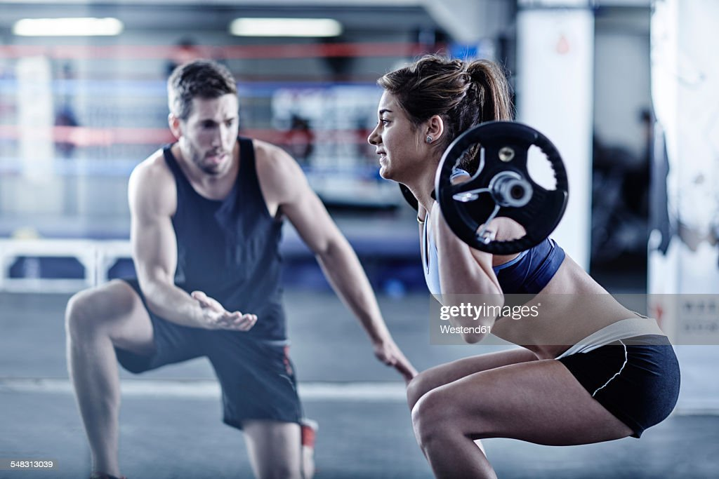 Trainer watching woman doing fitness training with weights : Stock Photo