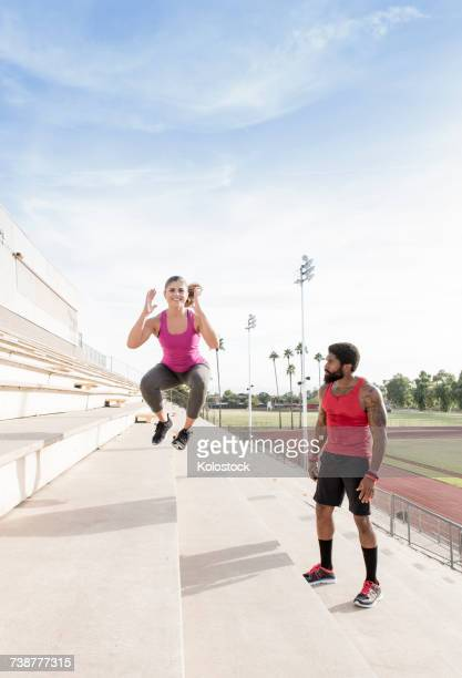 Trainer watching woman jumping on bleachers