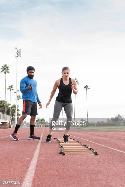 Trainer watching woman running ladder