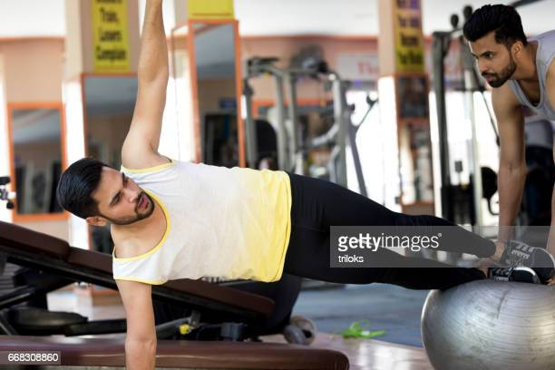 Trainer with young man in side plank pose