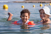 Grandmother teaching her granddaughter to swim at sea beach. Child wearing inflatable armbands / water wings / swimmies / floaties to keep buoyancy to float. Infant learning to swim by trainer help.