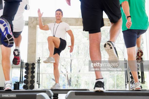 Trainer working out with class in gym