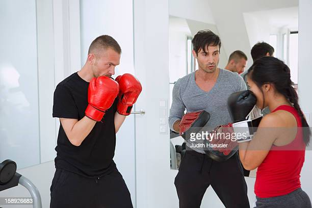 Trainer working with boxers in gym
