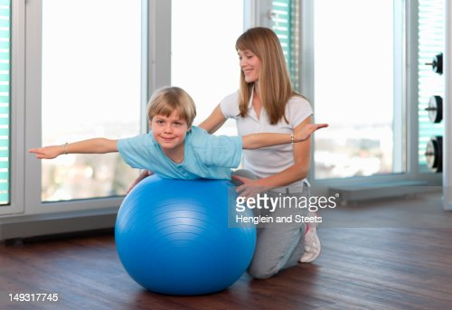 Trainer working with boy in gym : Stock Photo