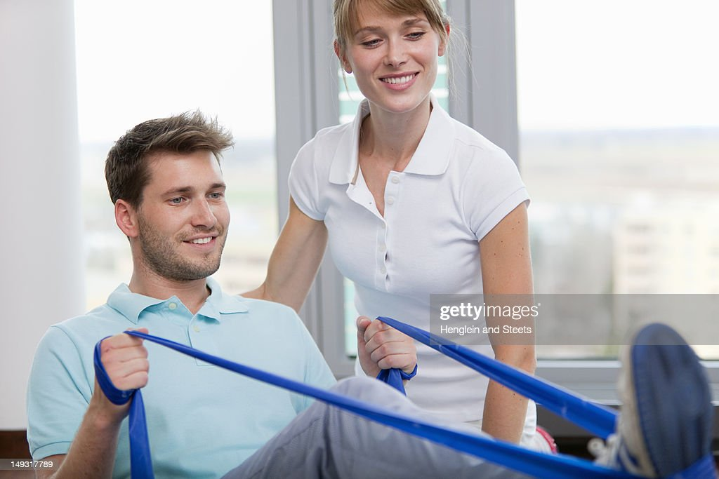 Trainer working with man in gym : Stock Photo