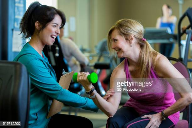 Trainer working with Senior woman in rehabilitation or exercise center