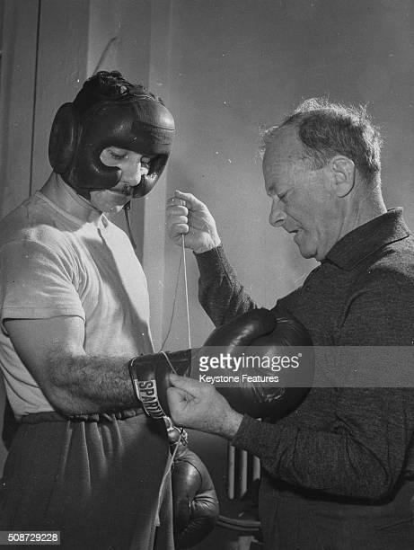 Trainer Zsigmond Adler preparing boxing champion and Olympian Laszlo Papp for a training session at the punch bag circa 1958
