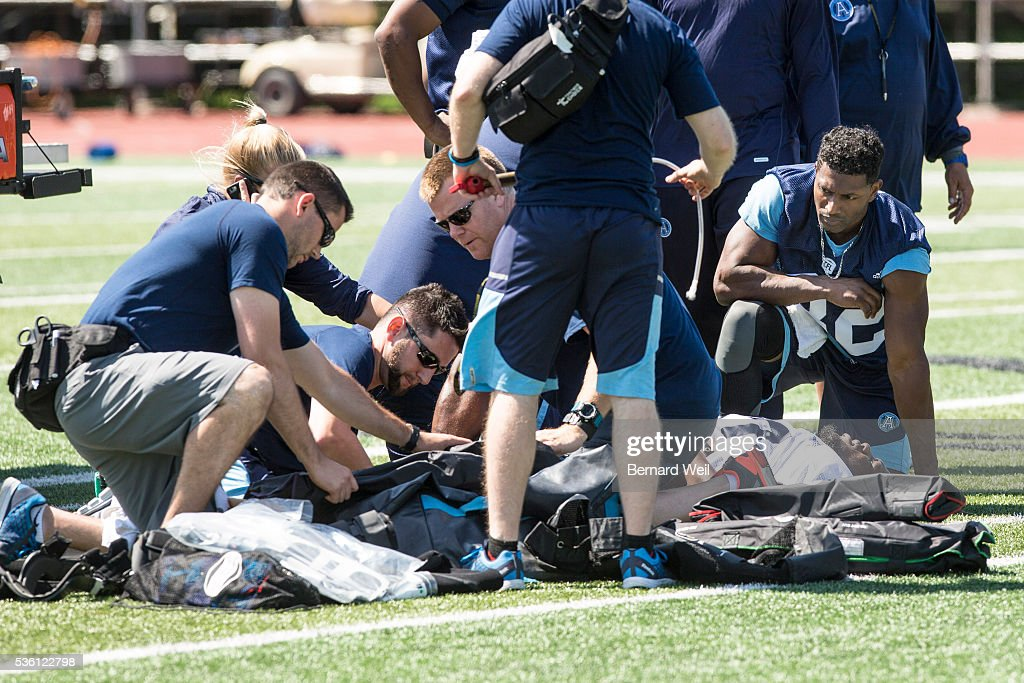 GUELPH, ON - MAY 31 - Trainers attend to linebacker Kanorris Davis while slotback Andre Durie consoles him during a Toronto Argonauts practice at Guelph University. May 31, 2016.