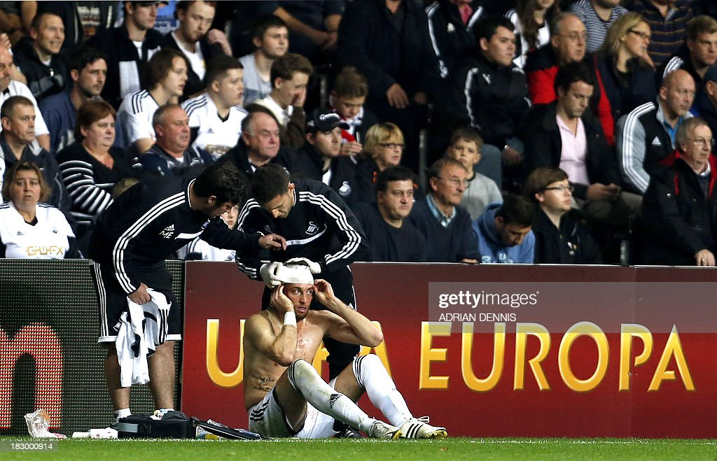 Trainers bandage Swansea City's Spanish midfielder Miguel Michu after his head was cut during the Europa League Group A football match between Swansea City and FC St Gallen at The Liberty Stadium in Swansea on October 3, 2013.