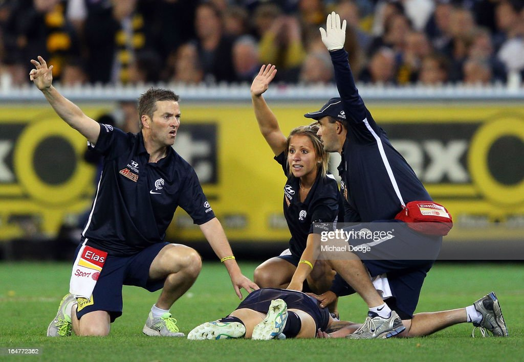 A Trainers call for the stretcher as Mitch Robinson (R) of the Blues lies on the ground during the round one AFL match between the Carlton Blues and the Richmond Tigers at Melbourne Cricket Ground on March 28, 2013 in Melbourne, Australia.