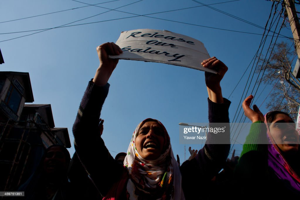 Trainers (Preraks) employed under Sakshar Bharat Mission , a scheme sponsored by Indian government hold a placard as they shout slogans during a protest against the government for not paying their salaries on December 30, 2013 in Srinagar, the summer capital of Indian administered Kashmir, India. Dozens of Preraks employed under the scheme, sponsored by the Indian government, were injured after Indian police attempted to disperse the crowd using batons. The group was protesting against the Government for non-payment of their honorarium, due for the last two years.