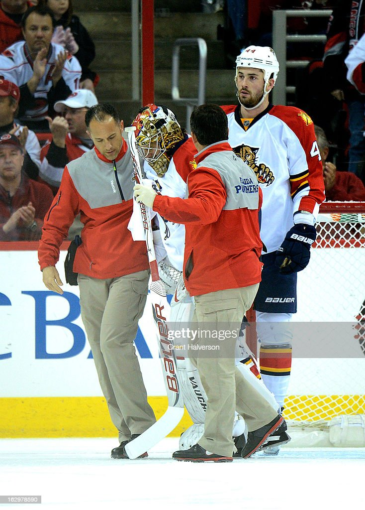 Trainers help Jose Theodore #30 of the Florida Panthers off of the ice after he was injured against the Carolina Hurricanes during play at PNC Arena on March 2, 2013 in Raleigh, North Carolina.
