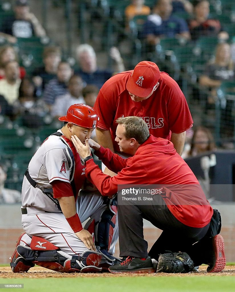 Trainers look at Hank Conger #16 of the Los Angeles Angels of Anaheim after taking a ball to the face against the Houston Astros in the ninth inning on September 15, 2013 at Minute Maid Park in Houston, Texas.
