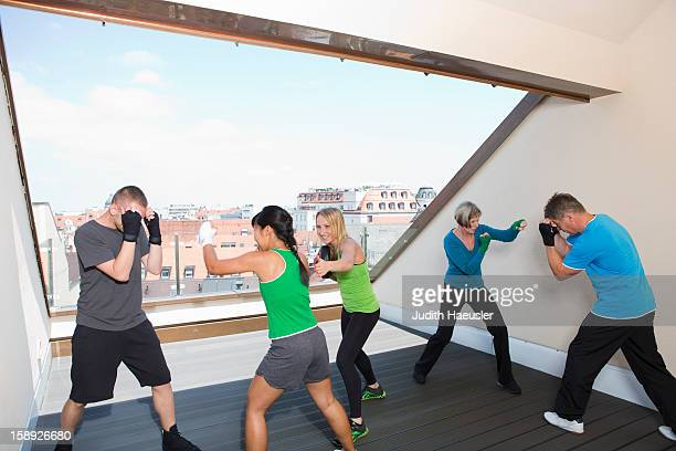 Trainers working with boxers in gym