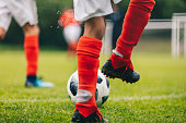 Football Players Kicking Ball on Grass Venue. Football Pitch Stadium in the Background. Soccer Player in Cleats and Red Soccer Socks. Football Practice Session