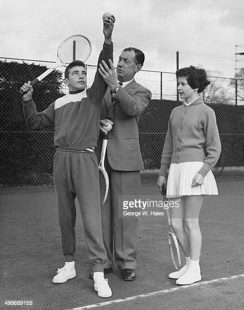 Training manager Dan Maskell coaches English junior tennis player Stanley Matthews on his serve at the Lawn Tennis Association's winter training...