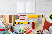 DIY training open manual with work tools, color swatches and painting rollers at bottom, top view