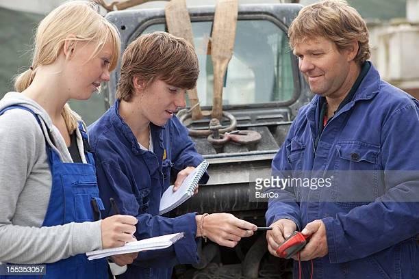 Training ein Mechaniker. Auszubildender macht Notizen.
