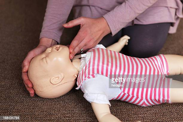 CPR training with baby doll laying on floor